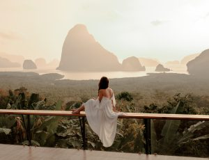 Woman with the white dress sit and see the mountain in early morning at the Sametnangshe Island viewpoint, Phang-Nga, Thailand.